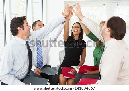 Business Team Giving One Another High Five - stock photo