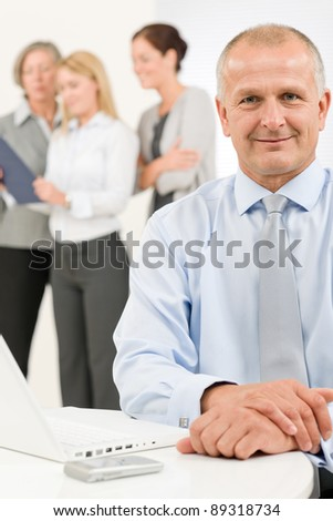 Business team happy mature businessman with attractive colleagues looking file