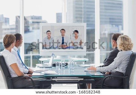 Business team having video conference with another business team in office