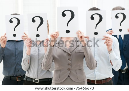 Business team hiding their faces behind question mark signs at office - stock photo