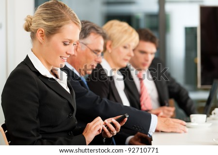 Business - team in an office; a woman is looking into the camera