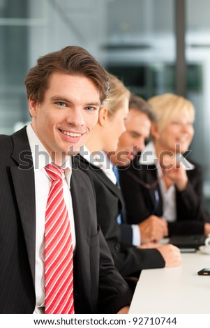 Business - team in an office; a young colleague is looking into the camera