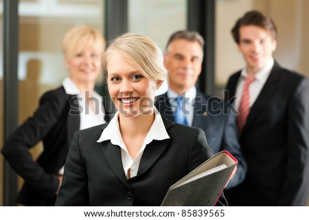 Business - team in an office; the junior manager is standing in front - stock photo