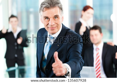 Business - team in an office, the senior executive has the thumb up, focus on thumb