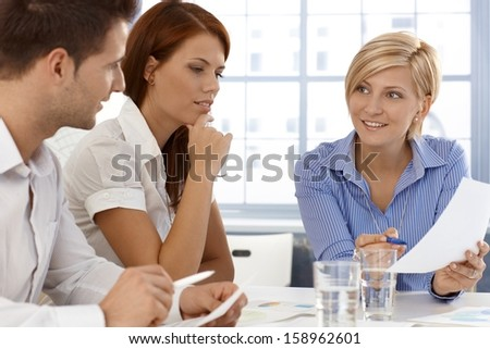 Business team in discussion of work document, working together in office.