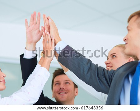 Business team joining hands together standing in office #617643356