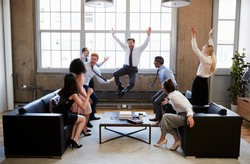 Business team jump for joy at hitting target in meeting