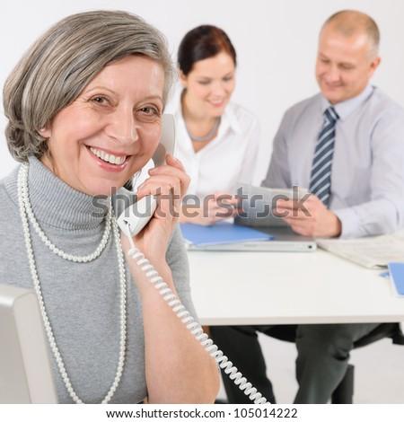 Business team meeting executive senior businesswoman calling on phone