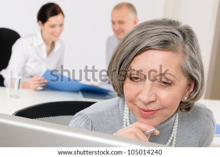 Business team meeting executive senior businesswoman with colleagues looking tablet