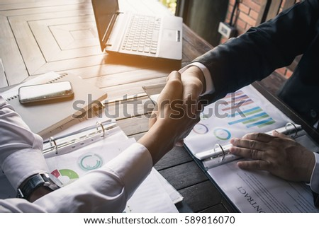 Business Team Meeting Handshake Applaud Concept. Business partners handshaking over business objects on workplace.