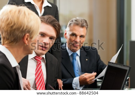 Business - team meeting in an office with laptop, the female boss with her employees