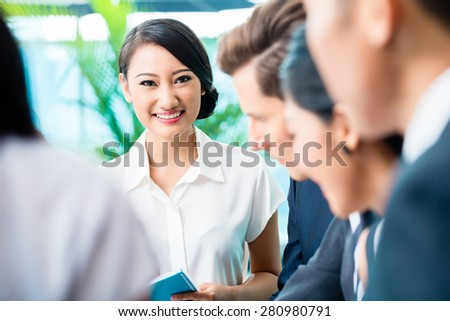 Business team meeting of Asian and Caucasian executives, Chinese woman is looking into the camera