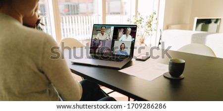 Business team meeting online over a video call on laptop. Woman sitting at table at home having a video conference with her colleagues.