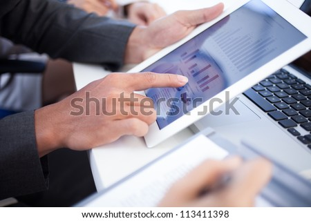 Business team meeting to discuss statistical data presented in the form of digital graphs and charts - stock photo