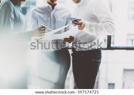 Business team meeting,work process.Photo professional crew working with new startup project.Project managers near window.Analyze business plans, smartphone hands. Blurred, film effect.Horizontal
