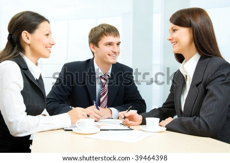 Business-team of three smiling people discussing new work