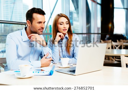 Business team of two in an office looking at some data on a laptop