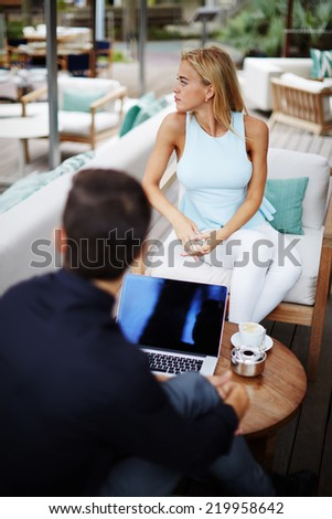 Business team of two success people sitting outdoors in lounge terrace and planning work, businessman and businesswoman meeting in modern place outdoors, business partners having meeting outdoors