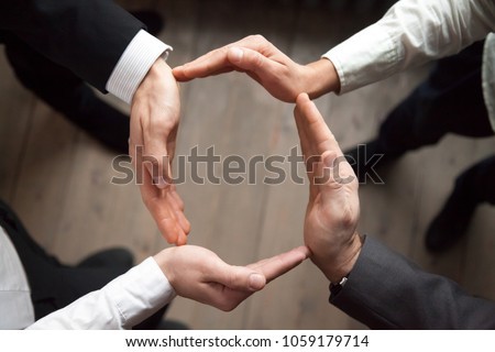 Business team people join hands forming circle, business protection, unity in care and support, shared corporate responsibility, help in teamwork, synergy trust safety concept, close up top view #1059179714