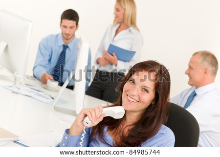 Business team pretty businesswoman holding phone happy colleagues around table