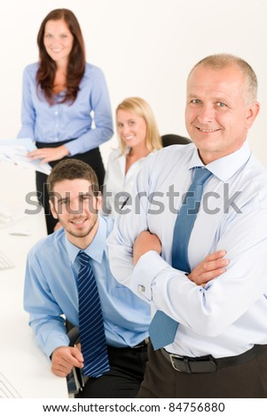 Business team senior businessman with attractive happy colleagues in office