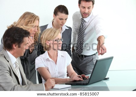Business team sitting around a laptop computer - stock photo