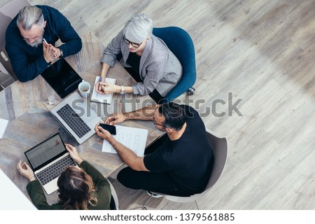 Business team sitting around a table and talking over new ideas. High angle view of corporate professional having a meeting in office.