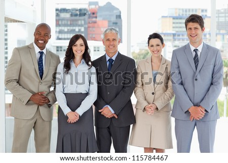 Business team smiling and standing upright side by side with their hands crossed