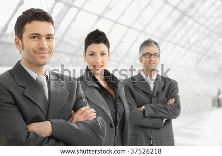 Business team standing in office hallway, looking at camera, smiling.