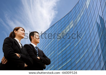 Business team standing together in front of modern building - stock photo