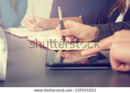 Business team taking notes on a meeting