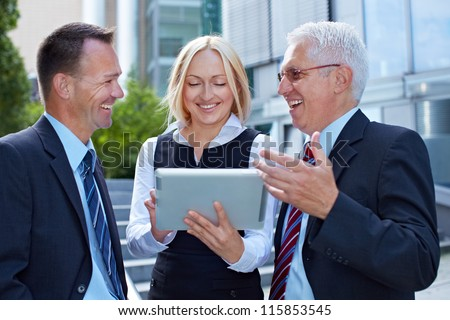 Business team talking and working with tablet computer outside