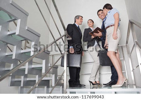Business team talking to each other in office stairway