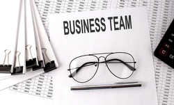 BUSINESS TEAM text on the paper with chart and office tools , business concept