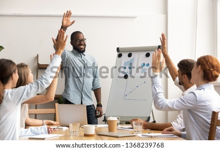 Business team voting concept, smiling african coach leader and diverse employees group raise hands up engaged in volunteering making unanimous decision participate in corporate presentation training