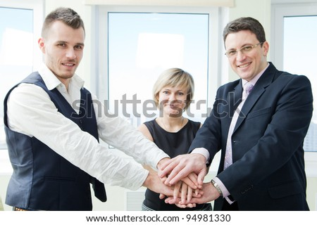 business team with their hands together in office interior.
