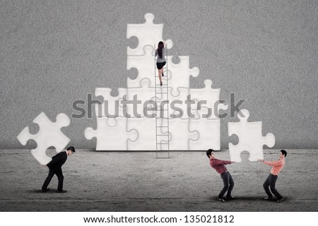 Business team work  building puzzle symbolizing working together finding  solutions to a problem