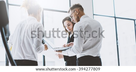 Business team work process. Photo professional crew working with new startup project. Project managers meeting. Analyze business plans laptop. Blurred background, film effect. Wide