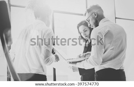 Business team work process. Photo professional crew working with new startup project. Project managers meeting. Analyze business plans laptop. Blurred background, film effect, black white. Horizontal