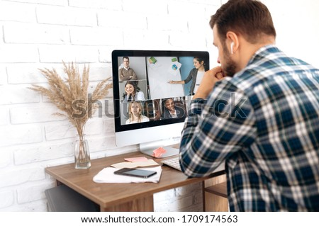 Business team working from home in a video conference. The guy communicates via video call communication with his business colleagues about the future strategy. Distant work