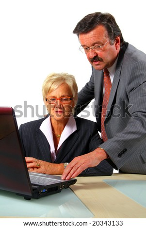 Business Team Working In Office A business woman and a man in front of a laptop on a desk. The man explains something to the woman. Isolated over white.