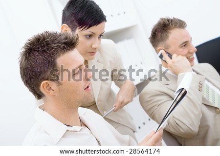Business team working together in office. Man and woman reviewing notes in the foreground, happy man talking on mobile phone in the background.