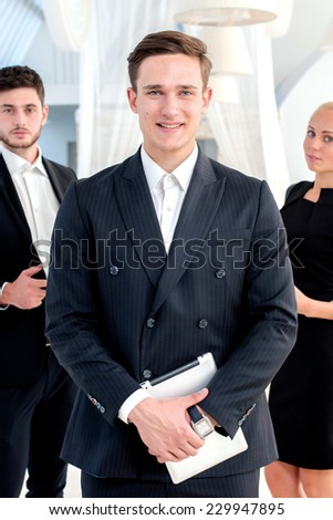 Business team. Young man in formal wear holding a the tablet and smiling at the camera while his colleagues are with laptop and mobile phone on the background