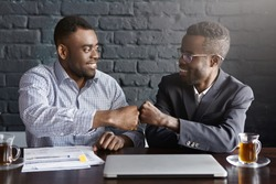 Business, teamwork and collaborataion concept. Two dark-skinned businesspeople in formal wear giving each other fist bump after successful agreement at meeting, happy with signing profitable contract