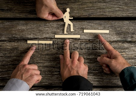 Business teamwork and cooperation concept with the hands of four businesspeople supporting paper cut outs of a man climbing the steps to success over rustic wood background.