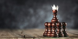 Business Teamwork Concept - Group Of Small Ambitious Pawns Working As A Team Holding Up Pawn With Fake Paper Crown Costume On Wooden table
