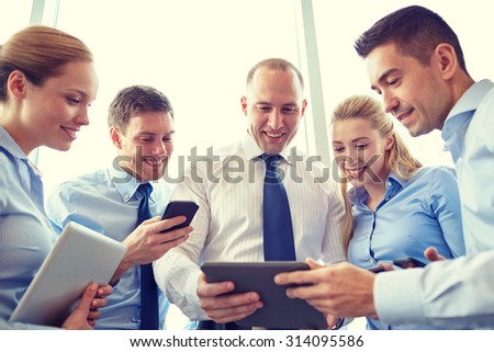 business, teamwork, people and technology concept - business team with tablet pc and smartphones meeting in office #314095586