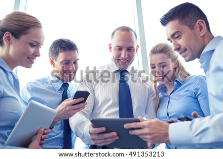 business, teamwork, people and technology concept - business team with tablet pc and smartphones meeting in office #491353213