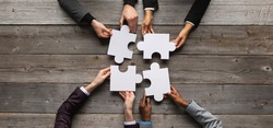Business teamwork with white puzzle of four pieces cooperation unity concept