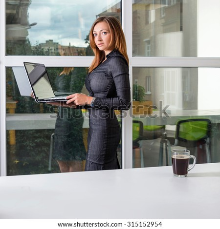 Business, technology and green office concept - young successful businesswoman with laptop computer at office. Woman using tablet computer or having a coffee break